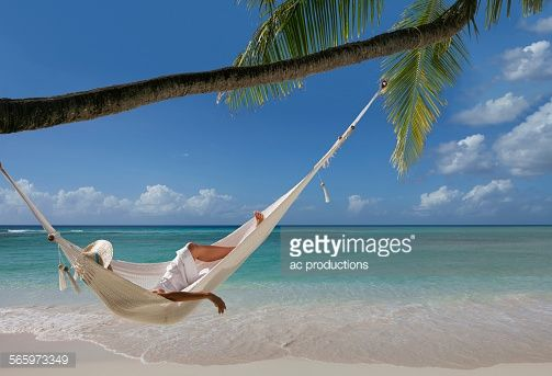 Stock Photo : Caucasian woman laying in hammock under palm tree on tropical beach