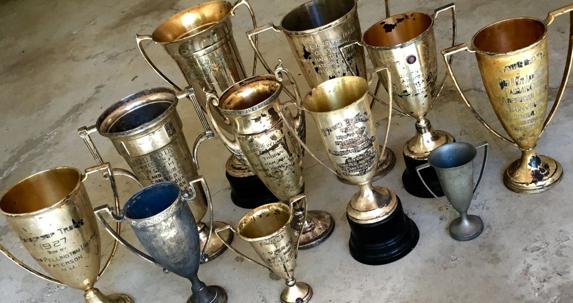 Antique trophy collection with various recognitions in various sizes.