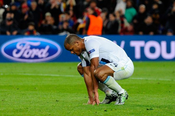 A dejected Manchester City captain Vincent Kompany reacts following his team's 2-1 defeat during the UEFA Champions League Round of 16, second leg match between FC Barcelona and Manchester City at Camp Nou on March 12, 2014 in Barcelona, Catalonia.