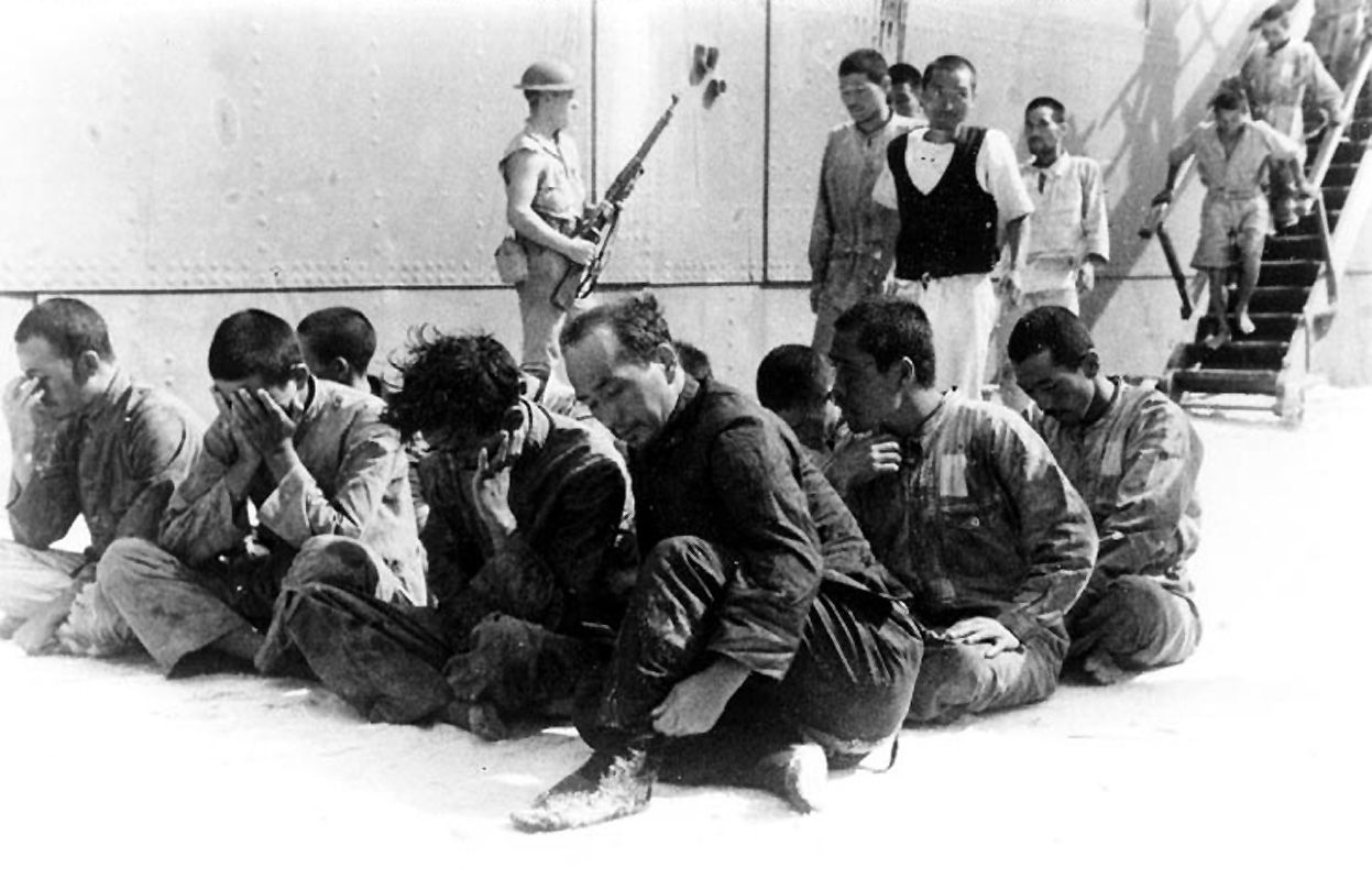 japanese prisoners of war under guard on midway, following their