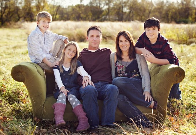 family portrait in a field on a red couch | Photo shoot ideas for ...