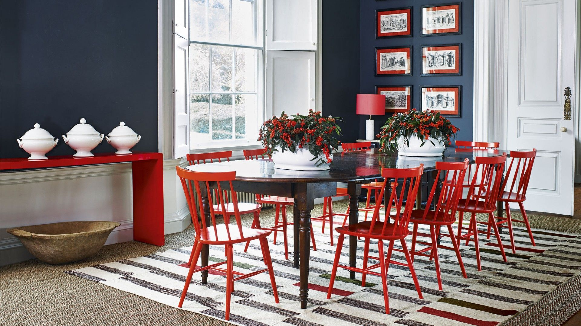 Be brave in your dining room with the brightest of reds on furniture and accessories. Chairs, console and framed antique prints punctuate this rich grey interior in no-holds-barred cadmium. The grand proportions of the room carry off this striking combination with aplomb.