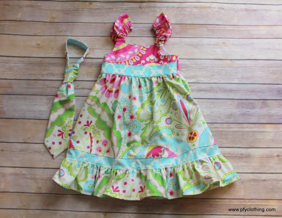 "Handmade outfits for your big girl and her brother. The dress comes in sizes 0-12yr. It has elastic sleeves for easy on and off. Ties are made with a simple velcro collar for easy on and off. Choose from a bow tie or necktie. necktie sizes are (0-2yrs, 3-5yrs, 6-9 yrs) bow tie sizes are small (baby-toddler), medium 4-6, large 7-12yrs  I use quality fabrics that are machine washable and dried on low heat.I finish all seams with a ""serger"", which makes my clothing much more durable and…"