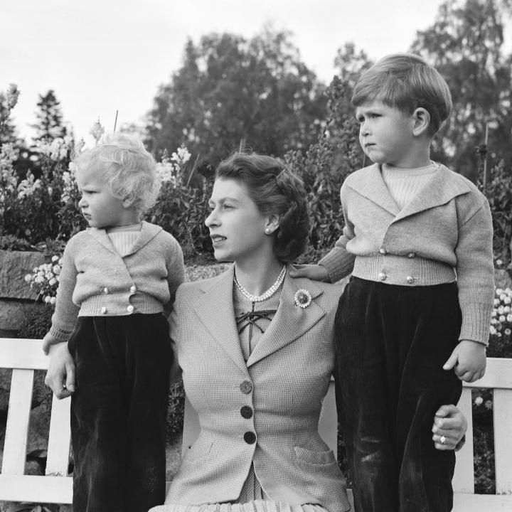 The Queen with Prince Charles and Princess Anne in the grounds of Balmoral Castle, Scotland. Charles is celebrating his 4th birthday (1952)