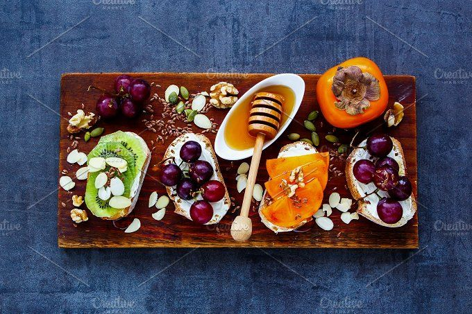 #Toast pieces set  Delicious toast pieces set. Wholegrain baguette slices with cream cheese various fruit honey seeds and nuts for breakfast. Slate background and top view. Clean eating vegetarian dieting concept
