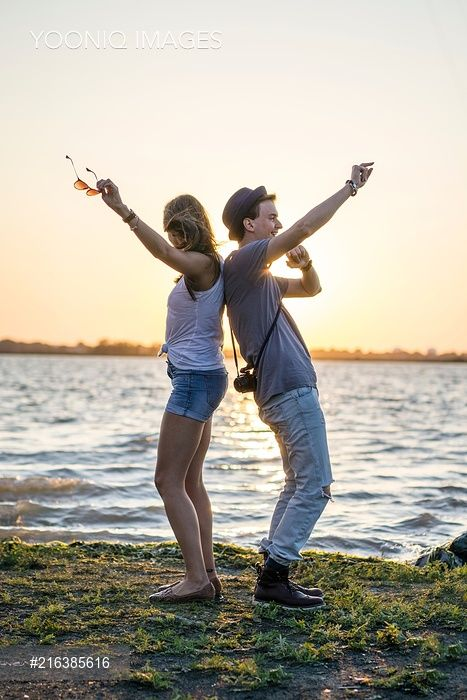 Yooniq images - Young couple back to back, raising arms by sea at sunset