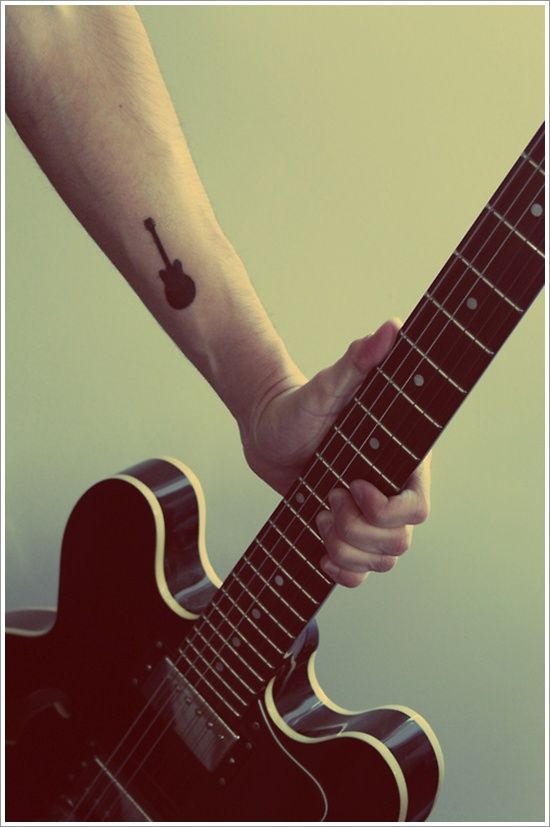 A Very Cute Guitar Tattoo On The Arm Minimalist In Design The Guitar Also Has This Matte And Full Colored Guitar Tattoo Design Tattoos For Guys Music Tattoos