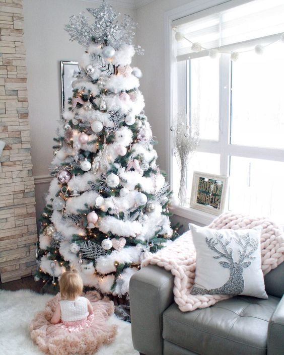 a Christmas tree decorated with white and silver ornaments