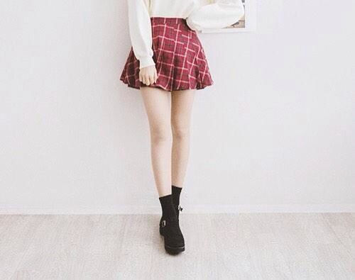 Plaid skirt with white sweater.