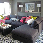 living rooms - charcoal gray sectional sofa chaise lounge charcoal gray walls glossy black modern coffee table gray cabinets david Hicks La Fiorentina bolster pillow hot pink pillows white lacquer tray David Hicks La Florentina Jonathan Adler Greek Key Rug