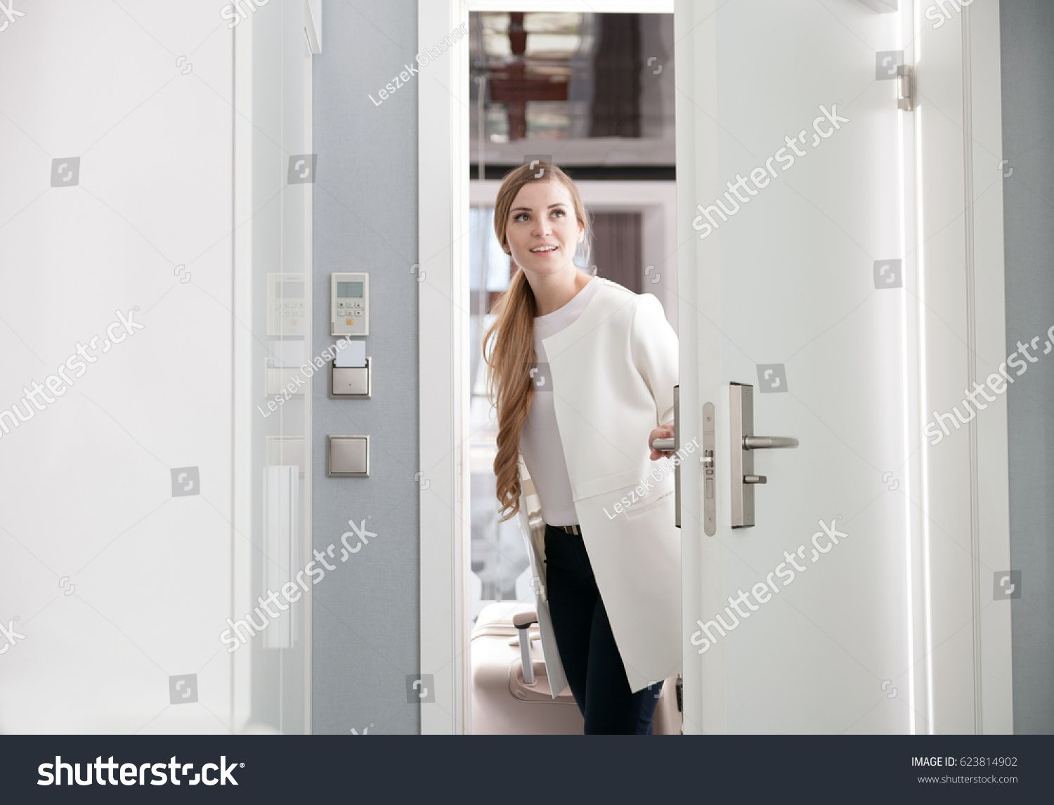 Young Delighted Woman With Suitcase Opening Door At Modern Hotel