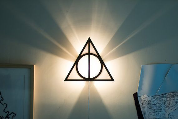 """Show that you know the """"Tale of the Three Brothers"""" with a sign of the Deathly Hallows wall lamp."""