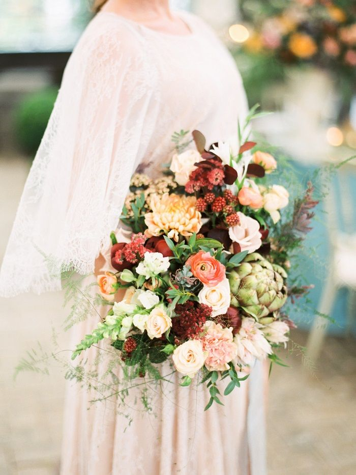 Soft beige shade wedding dress and deep wine shades bouquet | fabmood.com