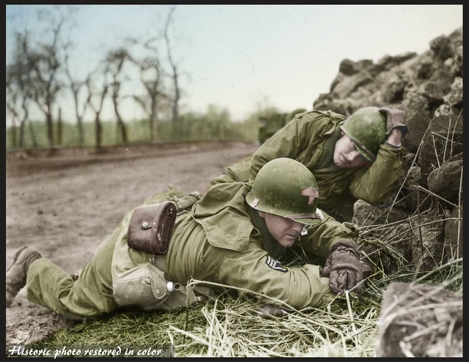 Two medics of the 274th Infantry Regiment, 70th Infantry Division take cover during a German artillery bombardment near Behren, France on February 17, 1945.