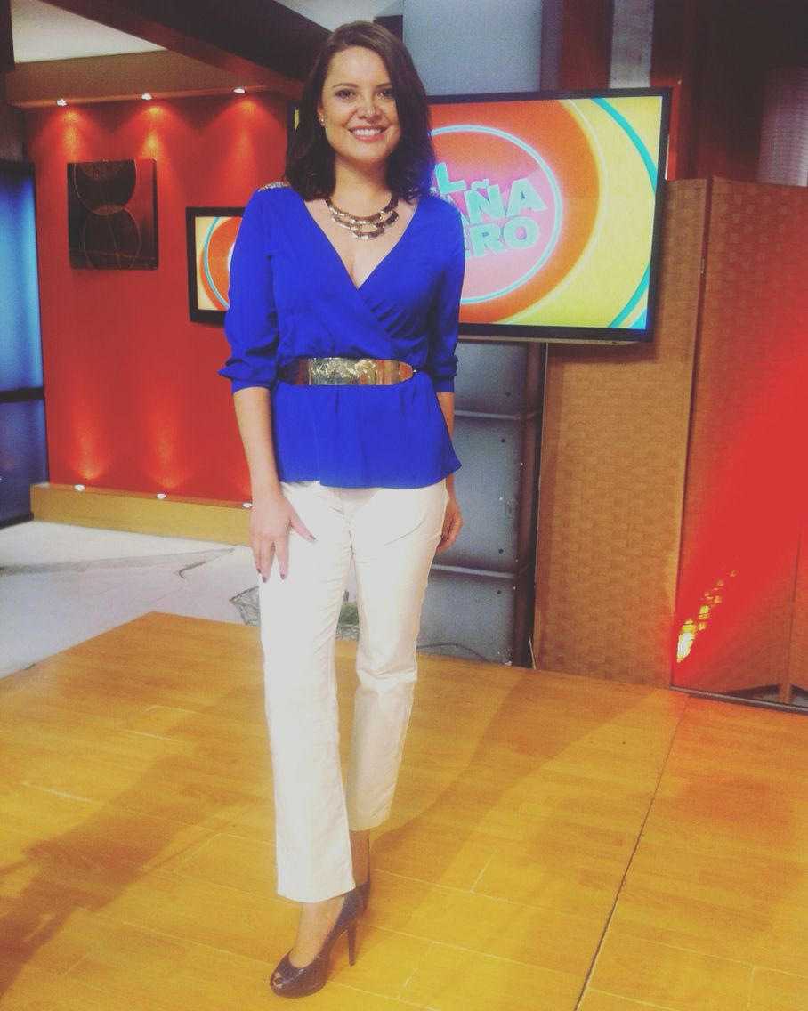Blusa azul de seda y pantalón blanco. Accesorios : cinturón placa dorada, collar dorado y zapatos azules.
