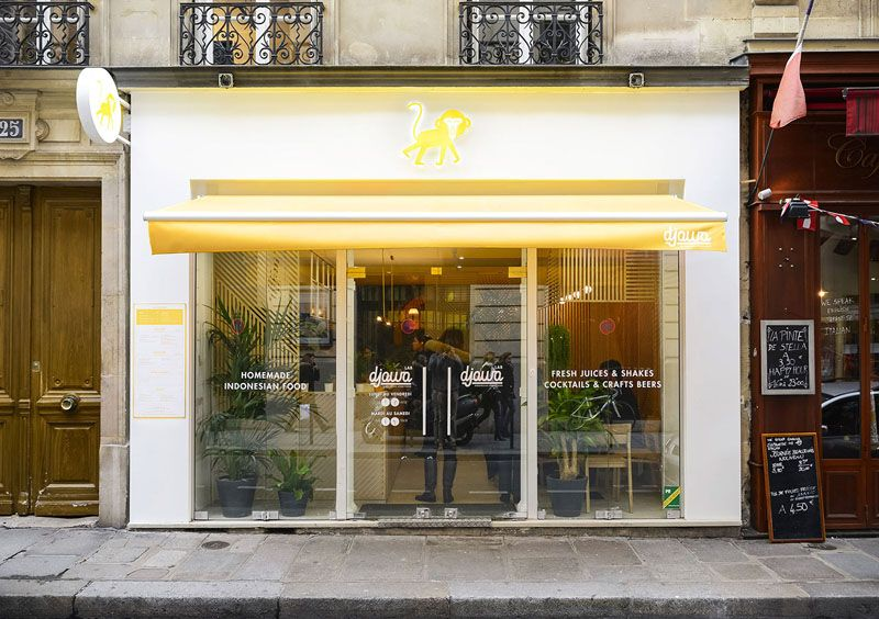 The Exterior Of This Contemporary Restaurant Is Bright White With Yellow Accents And Large Windows Glass Doors Allow People Walking By To Easily See