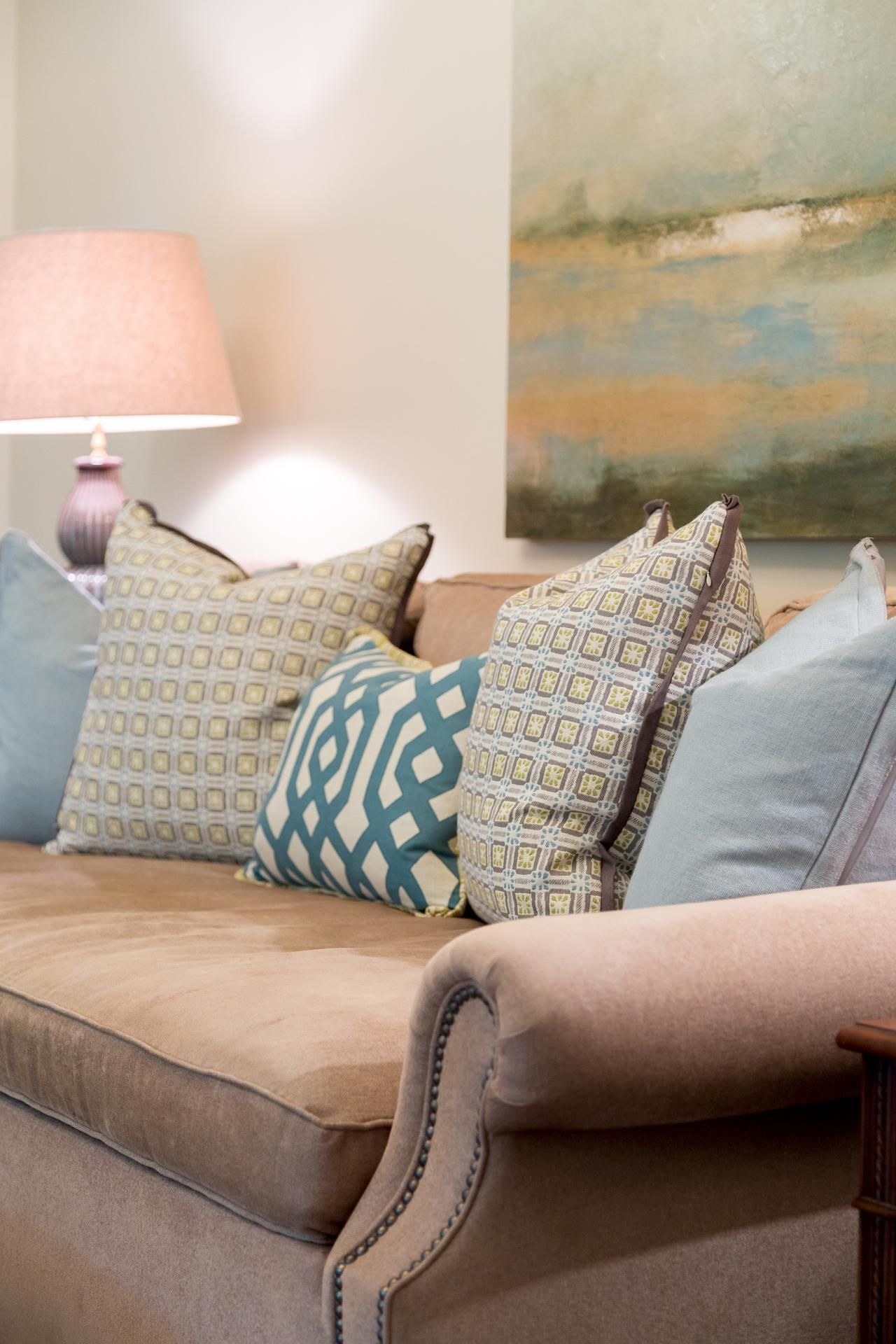 The lofty layering of multicolored throw pillows keeps the living