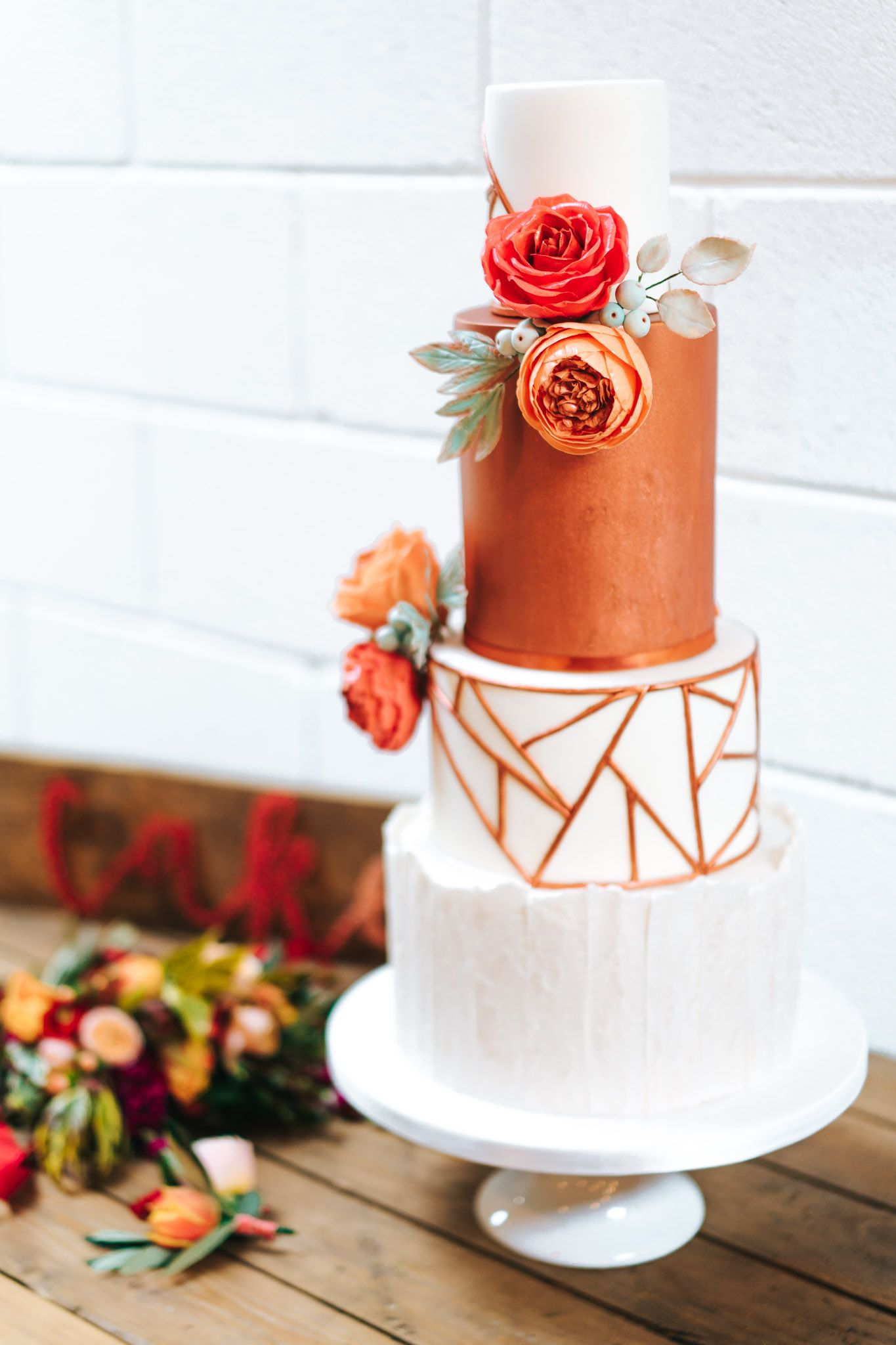 Copper geometric wedding cake with orange and red sugar flowers and ...
