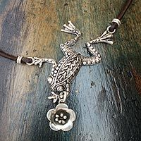 A charming little frog proffers a flower to his princess. It is said that her kiss will transform him into a handsome prince. Delightful sterling textures adorn the cheerful amphibian as Citlal Castillo upholds the world-renowned silver traditions of her hometown, Taxco. A leather cord completes the necklace. .925 Sterling silver
