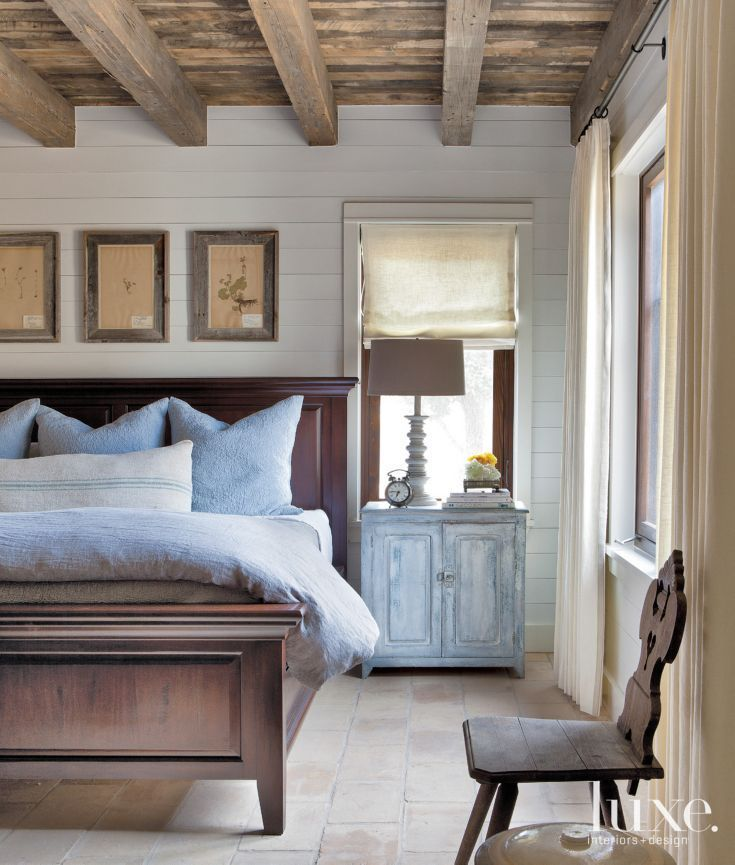 Cozy Bedroom With White Paneled Walls And Dark Wood Ceiling