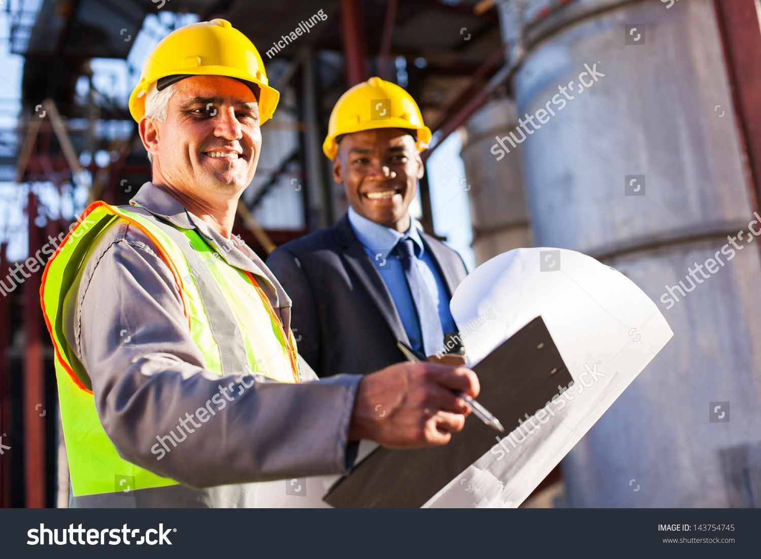 senior oil industry worker holding clipboard and blueprint