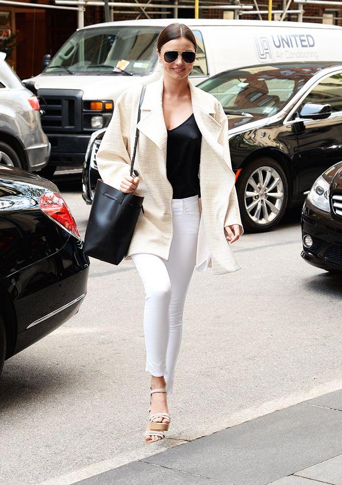 Miranda Kerr in a light beige coat, black top, white jeans, nude wedges, aviators, and black bag