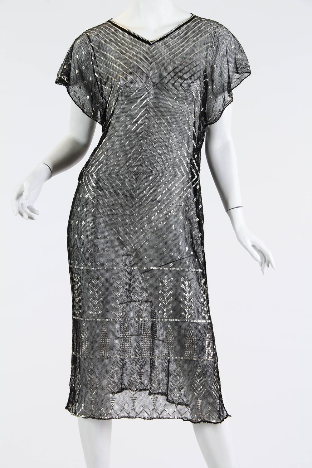 1920s Egyptian Assuit Metal and Cotton Net Dress. Hammered silver adorns the cotton net on this piece from the Art Deco era. Egyptian goods were quite in demand and these shawls were a luxury commodity. A lady with added hutzpah had hers made into a dress such as this one. These shawls were traditionally a cream colour and were draped over a bride at her wedding as wedding gifts as they held great monetary value being adorned with the precious metal. Today this tunic interestingly works…