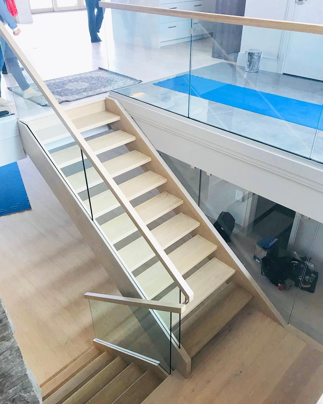 Closed 2 side white oak stairs with built in glass channel. For the level  guards we used the Q-line aluminum engineered base shoe with 12mm glass.