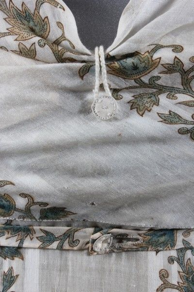 A printed muslin day dress, circa 1800-1810, self-striped and printed with foliate bands in shades of buff and blue, with apron-fall to bodice and skirt front, the bodice held in place by buttons and loops, empire line linen inner-bodice panels with draw-string, button fastened waistband, bust approx 28in, 71cm This dress has been on display at the Jane Austen museum over the last decade. Kerry Taylor Auctions Sale Name: Vintage and antique fashion and textiles February 7th 2012 Lot 81