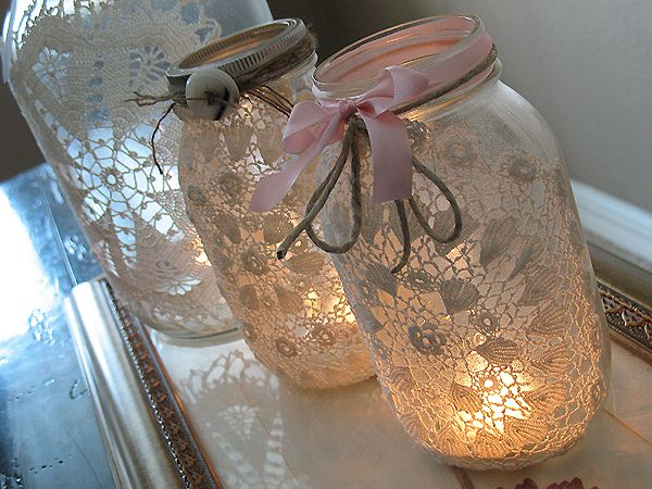 Fabric doileys are sprayed with adhesive and then wrapped around mason jars of varying sizes for a very romantic and rustic look!