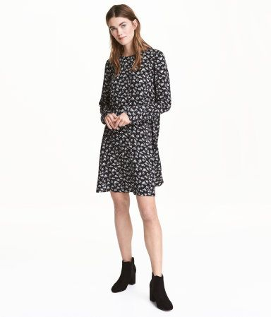 Black floral. Straight-cut, long-sleeved dress in woven fabric with a printed pattern. Seam at waist, opening at back of neck with button, and gently flared