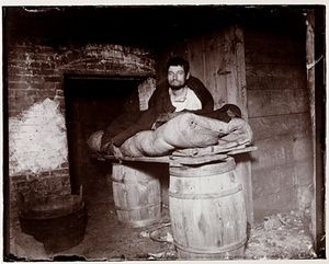A man on a makeshift bed make of a plank across two barrels taken in New York around 1890. He was one of four pedlars who slept in a cellar. The photograph was used in the exhibition Revealing New York's Other Half, by Jacob A. Riis.