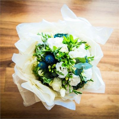 Good mixture of white flowers, foliage and sea holly - good balance. Tied with garden twine for a natural look.