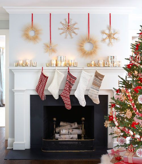 Scandinavian wreaths and large stars on long red ribbons are staggered above a fireplace