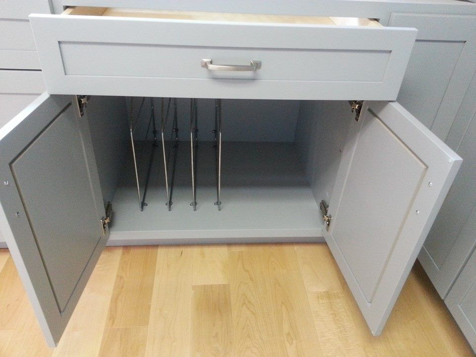 Left (sink) side: to the immediate right of sink. Wide drawer above cabinet with vertical dividers on one side and tall, open storage on the other.