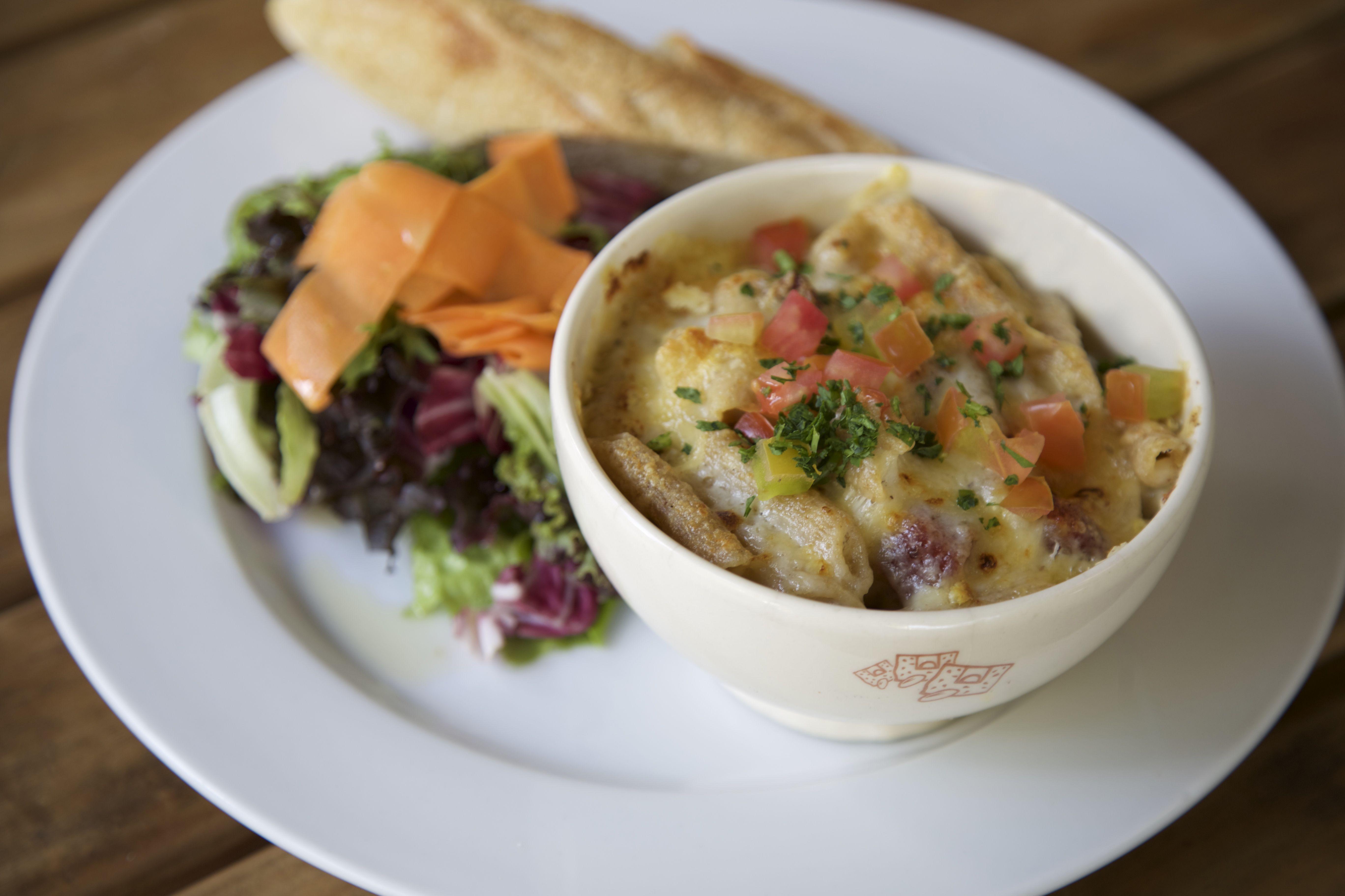 Mac and Cheese penne integral gratinado com molho cremoso de queijo e bacon, servido com baguete e mix de folhas