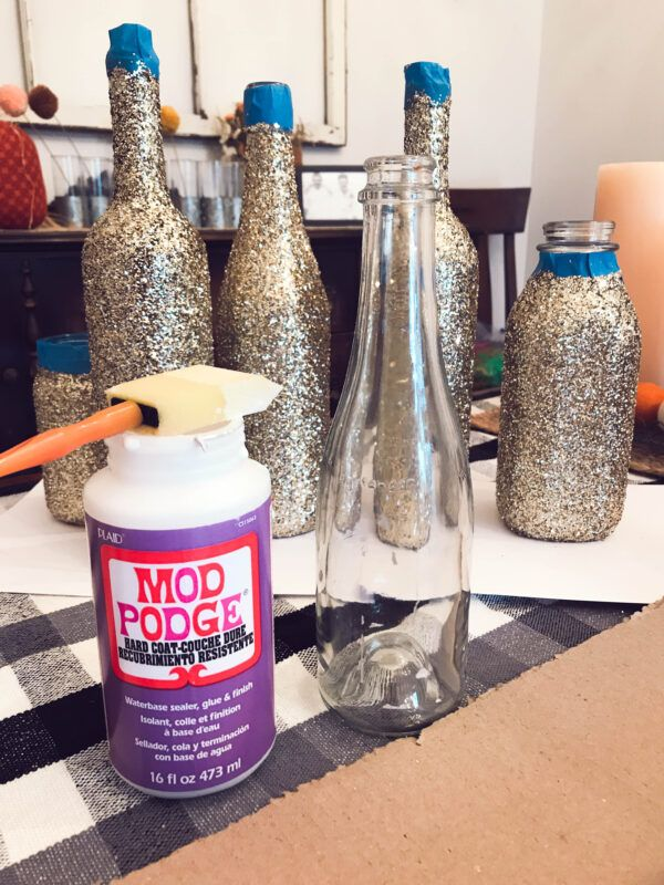 Tutorial for DIY Glittered Wine Bottles is part of Glitter wine bottles, Wine bottle diy crafts, Wine bottle diy, Wine bottle centerpieces, Glitter bottle, Glitter wine - Getting glittered wine bottles is as easy as 1, 2, 3! In a few easy steps, anyone can glitterup a wine bottle  This method also works for other glass too!