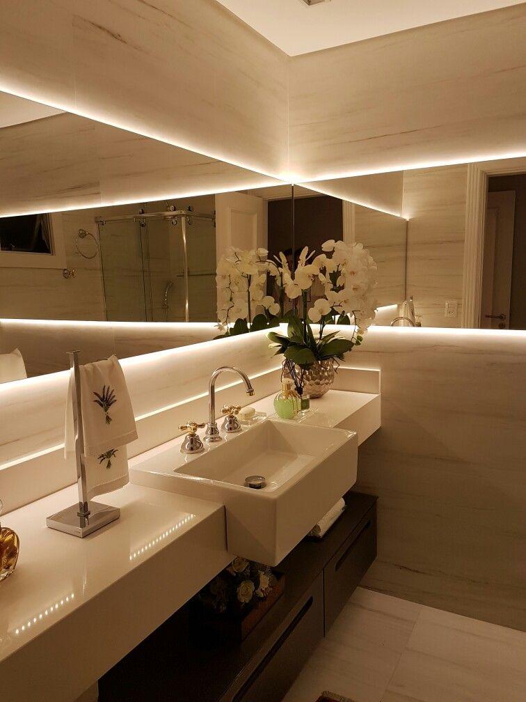 Banheiro com revestimento Travertino Portobello, espelhos com efeito infinito,iluminação indireta,móvel em vidro.