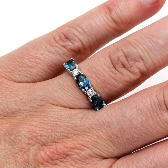 A gorgeous three stone London Blue Topaz band in a sophisticated east west design with sparkling conflict free natural diamonds. Blue Topaz is a