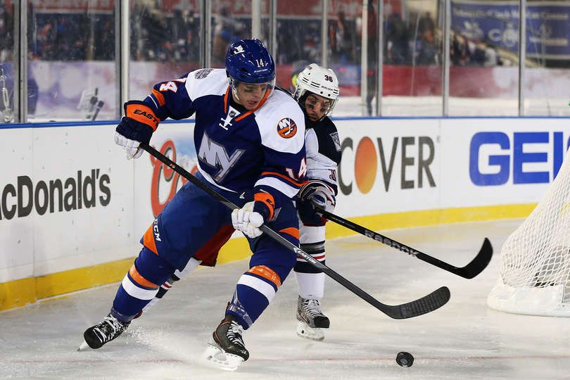 #Isles defenseman Thomas Hickey protects the puck from a Ranger player at Yankee Stadium.