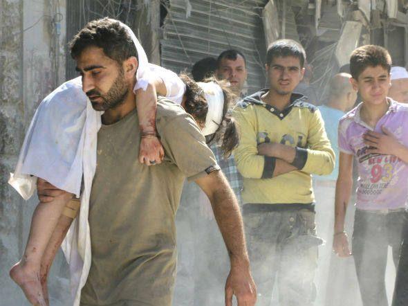 Homem carrega criança ferida após ataque das forças de Assad em Aleppo, Síria. (3/6/2014)