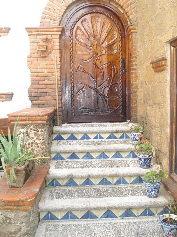 Escalera de concreto lavado y azulejos talavera; puerta en madera de encino labrada.