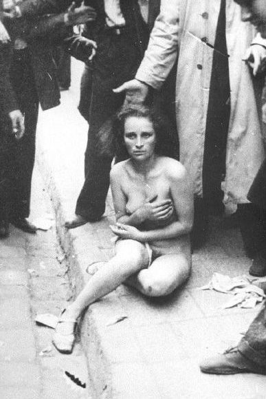 A Jewish girl is humiliated by bystanders on the streets of Lwow, Poland, 1941