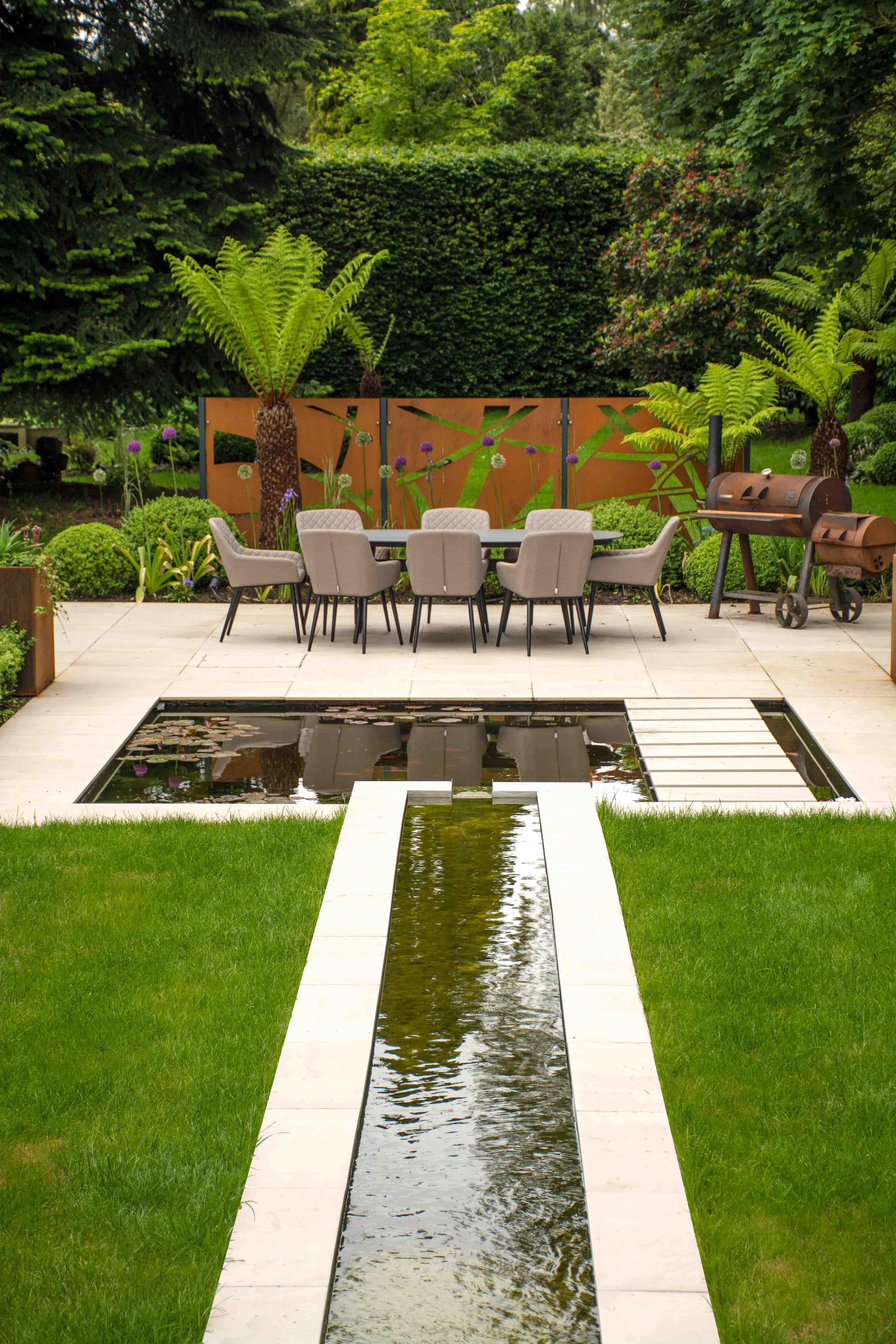 A Contemporary garden featuring a Water feature, Koi pond and Cor