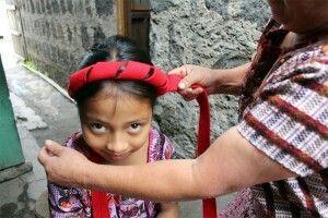 Magdalena coloca el tocoyal(parte de la indumentaria indígena en Santiago Atitlán) en la cabeza de Josefa Unbound.org ©