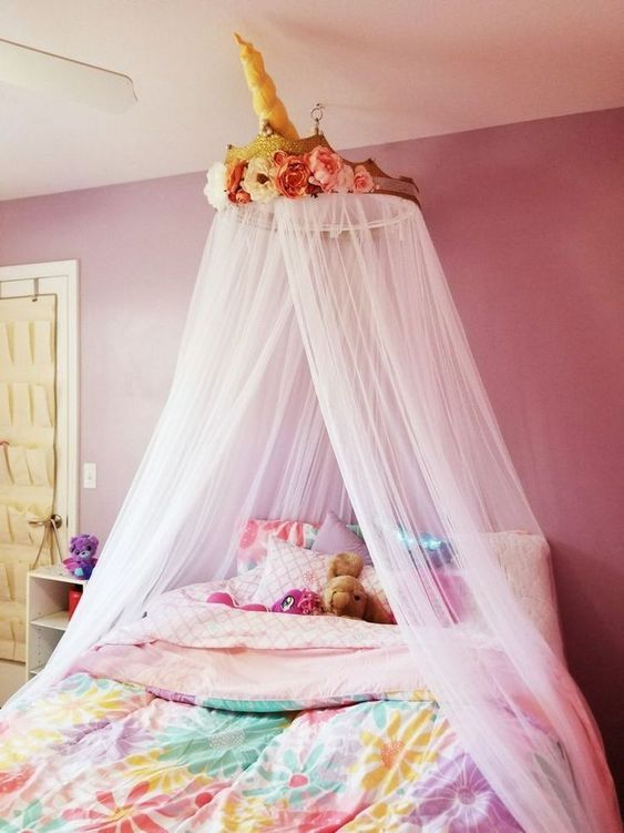 Pink girl's bedroom with a unicorn canopy with horn and flowers. #visionbedding #unicorns #homedecor #bedroomdecor #unicornbedrooms