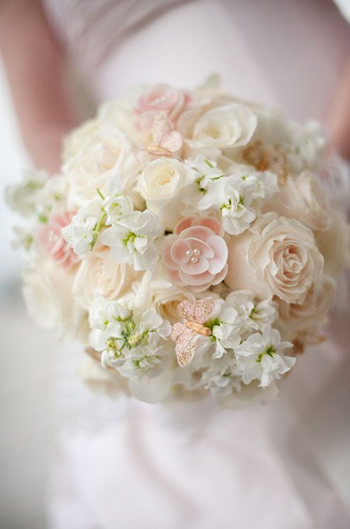 A Bouquet Of White Freesia And Blush Roses Is Accented
