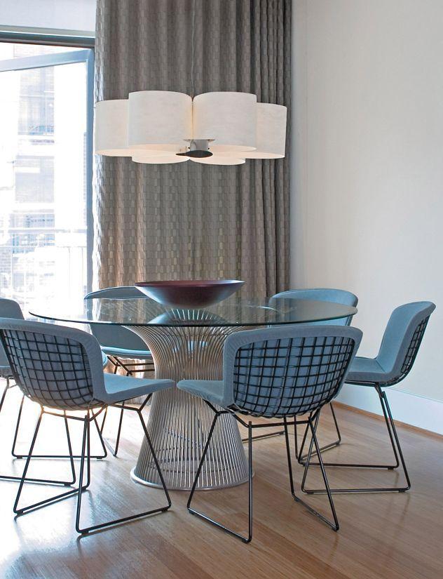 Une table en verre arrondie et ses chaises en tissu moelleux Salle