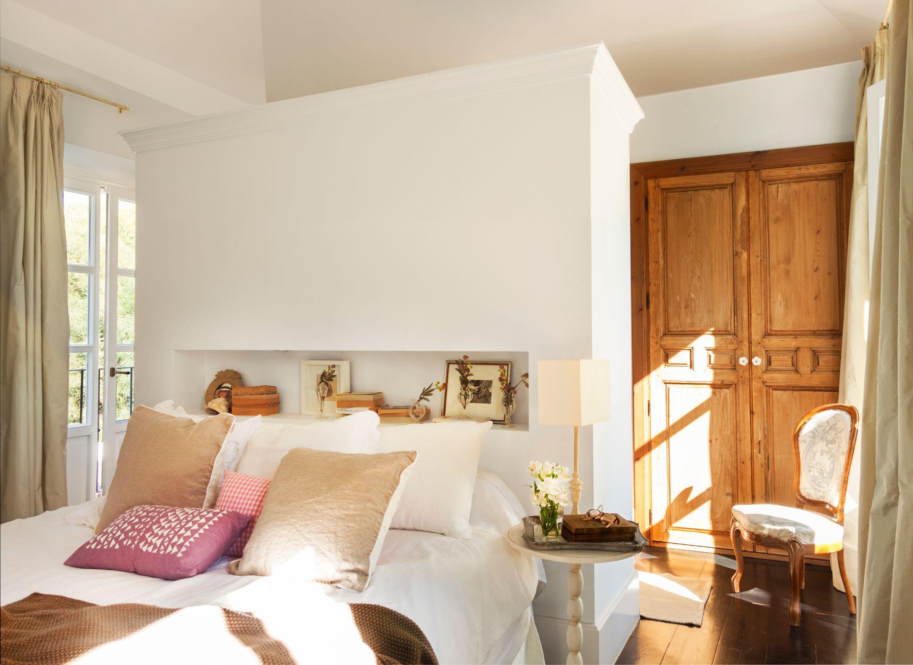 Cama apoyada en mueble de obra con hornacina y armario detrás ...