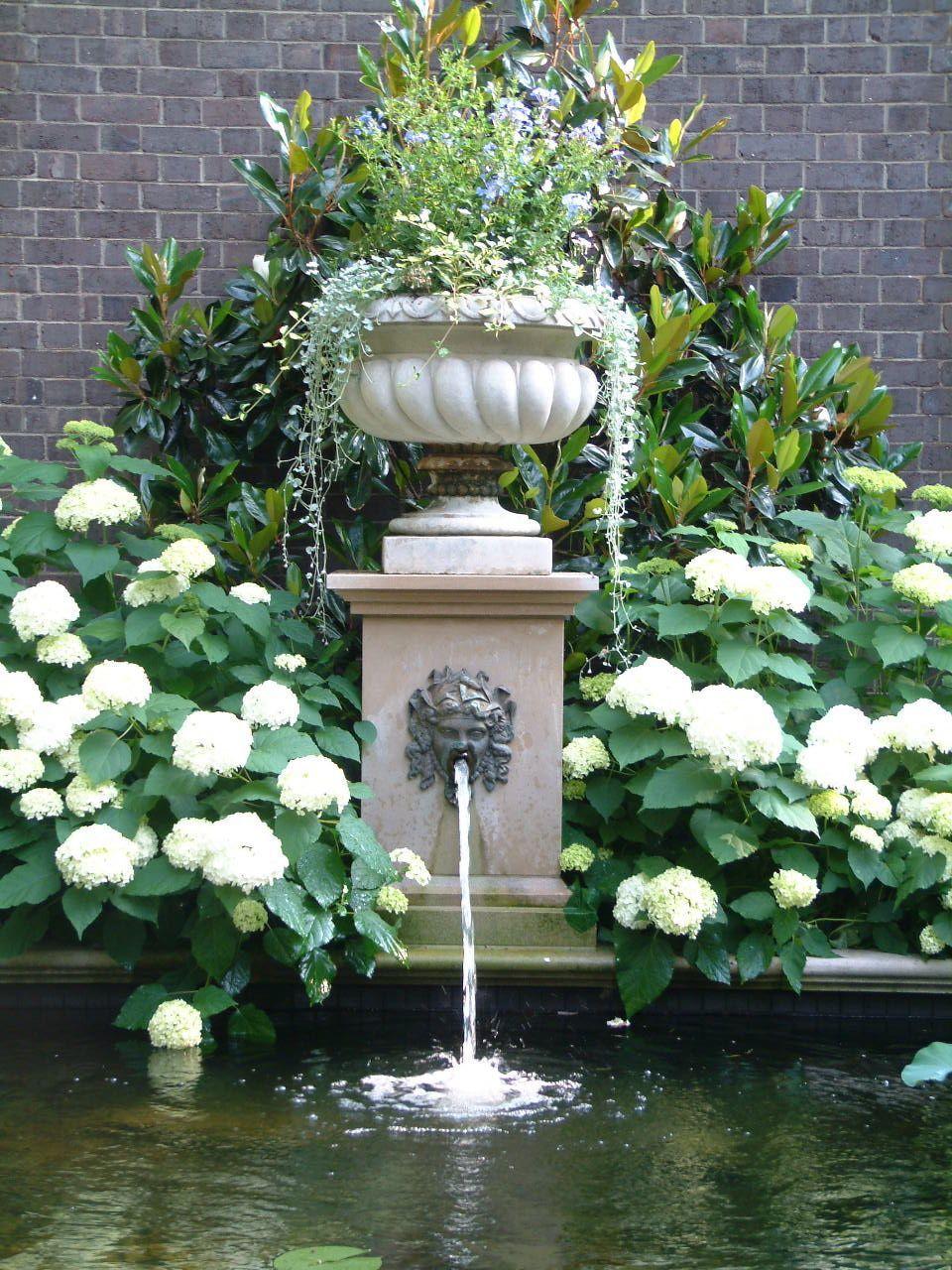 Garden pond with limestone & bronze details by Howard Design Studio.